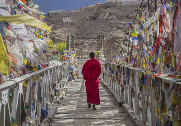 A monk walks on the bridge pathway surrounded by colorful tibetan prayer flags