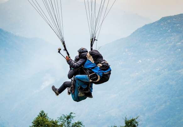 Delo,Darjeeling, India. Paraglider with tourist is starting to start his flight
