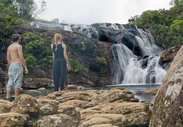 Couple enjoying the views of the glittering Ramboda Waterfalls in Sri Lanka