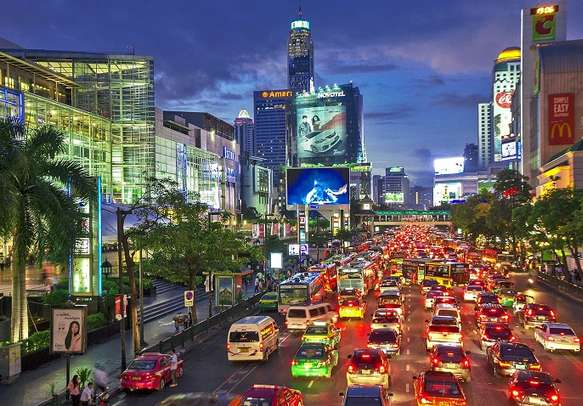 Cityscape of the MBK shopping mall in early night time with traffic