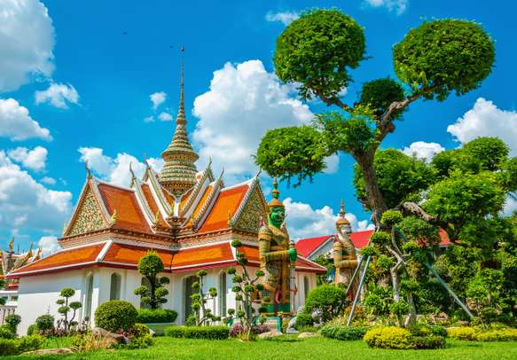 Great Palace Buddhist temple with famous green tree gardens in center of Bangkok.