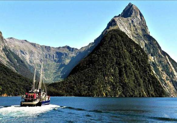 Tourists enjoy boating activities Milford Sound.