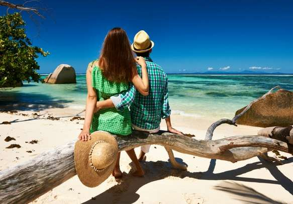 Couple relaxing on a tropical beach Anse Source d'Argent at La Digue in Seychelles.
