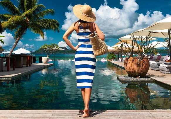 Woman in sailor striped dress near poolside jetty at Seychelles.