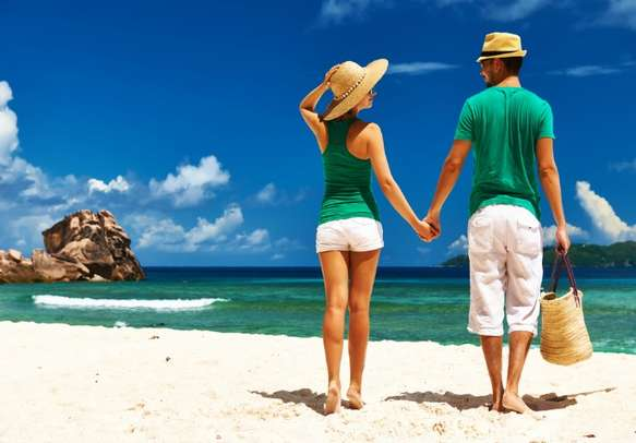 A couple takes a walk on tropical beach of La Digue in Seychelles.