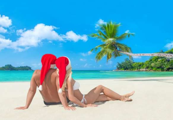 Romantic couple relaxes on a beach in the Baie Lazare district of Mahé island.