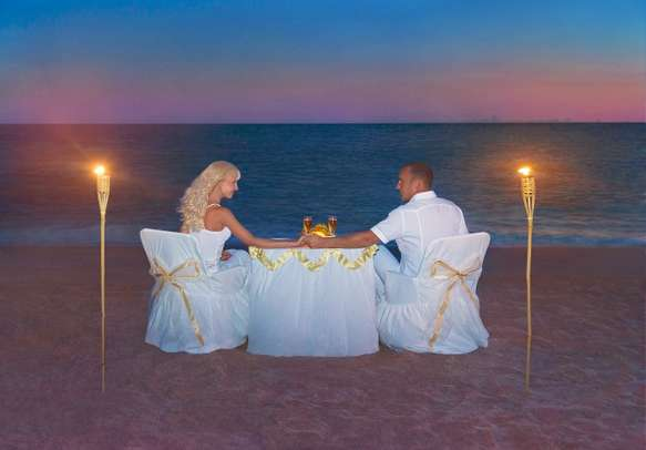 Couples enjoy a lavish dinner on a beach in Seychelles.