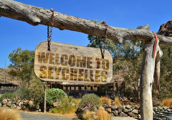 """Old vintage wood signboard with text """" welcome to Seychelles"""" hanging on a branch."""