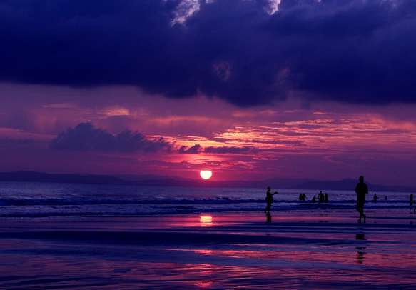 Couples enjoying romantic moments during sunset at Radhanagar Beach.