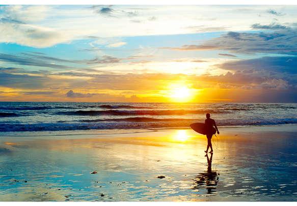 A surfer enjoys a quiet walk in Bali