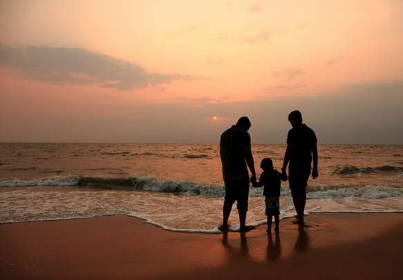 Silhouette of a kid and two adults playing on a beach.