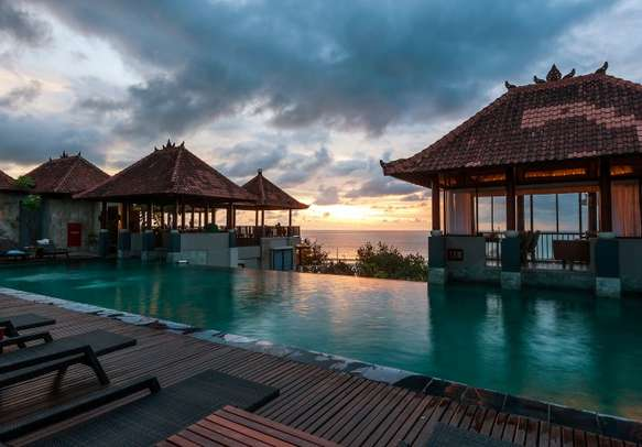 Enjoy the sunset at Kuta Beach in Bali from swimming pool view.