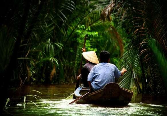 Vietnamese people paddling in the Mekong river.