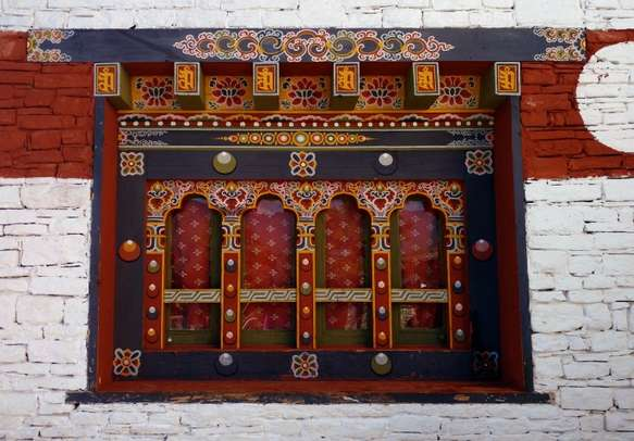 Colourful wooden window panels set in stone at Changangkha Monastery in Thimphu