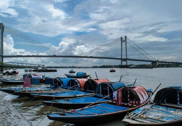 Vidyasagar Setu bridge with wooden boats on Hoogly river