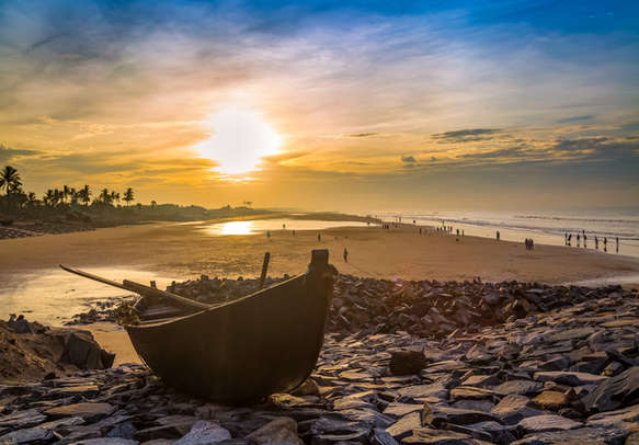 Wooden boat on the beach rocks at sunrise with vibrant moody sky