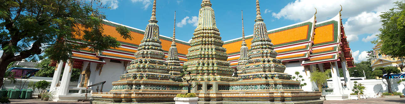 Great Palace Buddhist temple with famous green tree gardens in center of Bangkok
