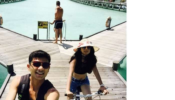 Nisarg and his wife cycling at their resort