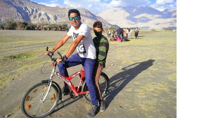 ninad riding bicycle with a local in ladakh