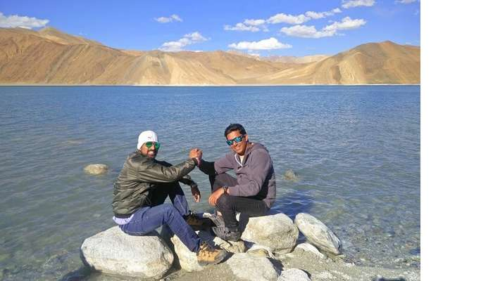 ninad and friend sitting near pangong lake