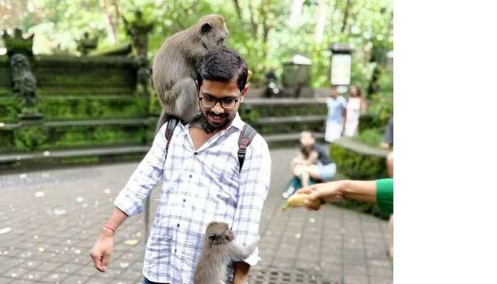 man posing with monkey in bali