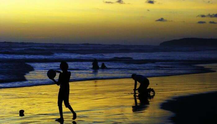 People playing at Ganpatipule beach in Maharashtra