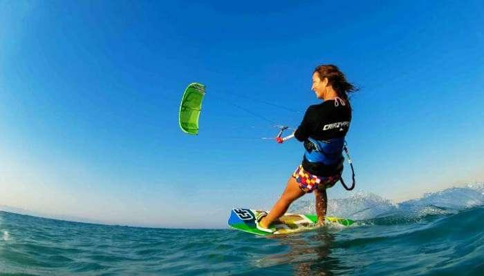 A free-spirited woman enjoys kiteboarding at Le Morne Beach Mauritius