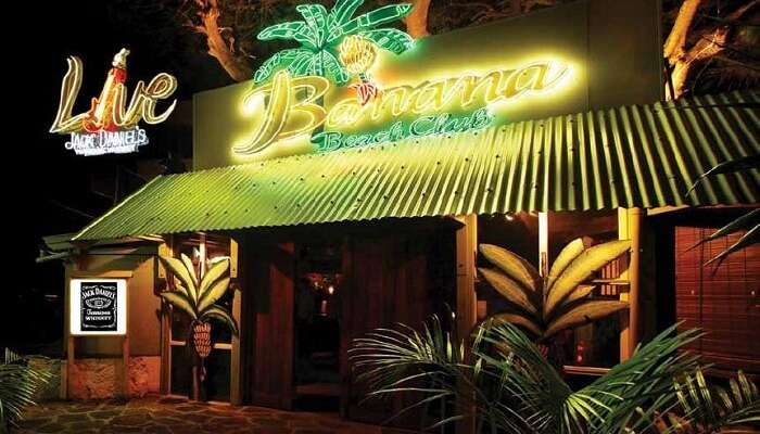 The glittering neon sign of Banana Beach Club attracts people to it