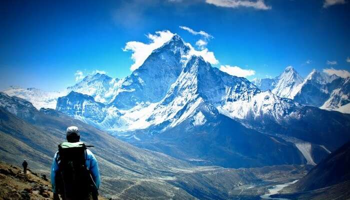 A trekker looks at the majestic Himalayan peaks covered with snow