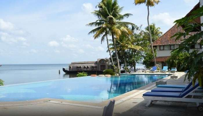 Infinity pool at Lemon Tree Vembanad Lake Resort with a view of the houseboat