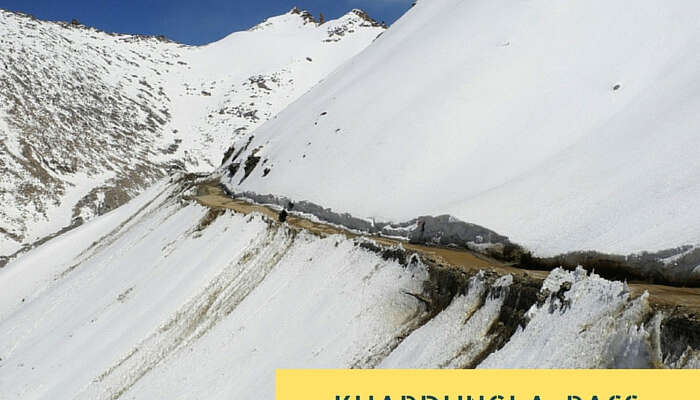 The narrow road amidst the snowclad mountains near Khardungla Pass that is the highest motorable road in the world