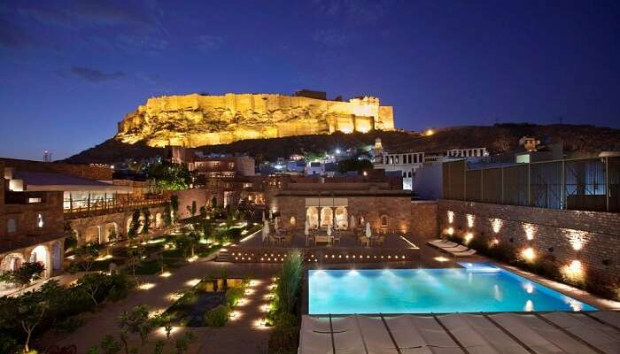 A night shot of the swimming pool at Rass Hotel with the Mehrangarh Fort in the backdrop