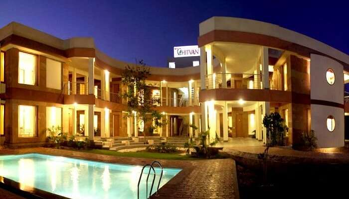 An evening shot of the swimming pool and the hotel building at the Chitvan Hotel in Ajmer