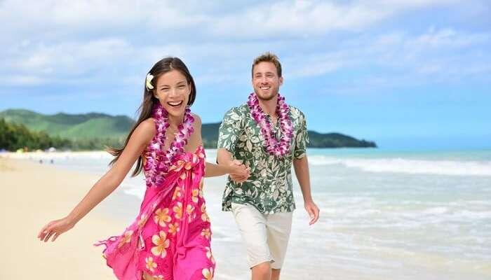Happy couple having fun on Hawaii beach wearing Aloha shirt and pink sarong sun dress and flower leis