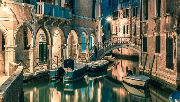 Lateral canal and pedestrian bridge in Venice at night with street light illuminating bridge and houses