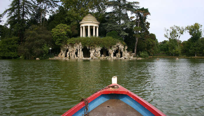 a rowboat in a river in front of temple of love