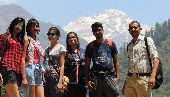 Young travelers pose in Kasol with the beautiful hills in the background