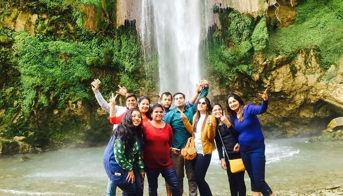 A group of travelers enjoying at the Tiger Falls in Chakrata on their weekend trip from Delhi