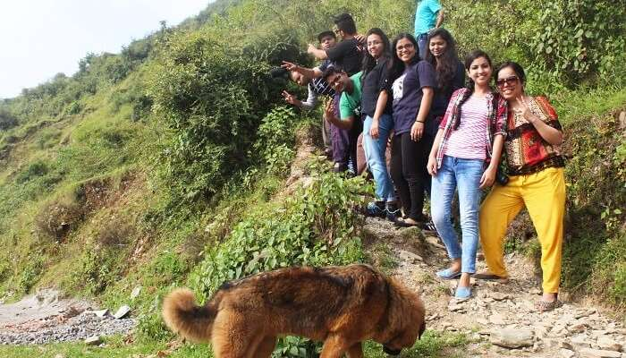 Travelers pose for a photgraph before continuing on their hike on a narrow trail on their weekend trip from Delhi to Chakrata