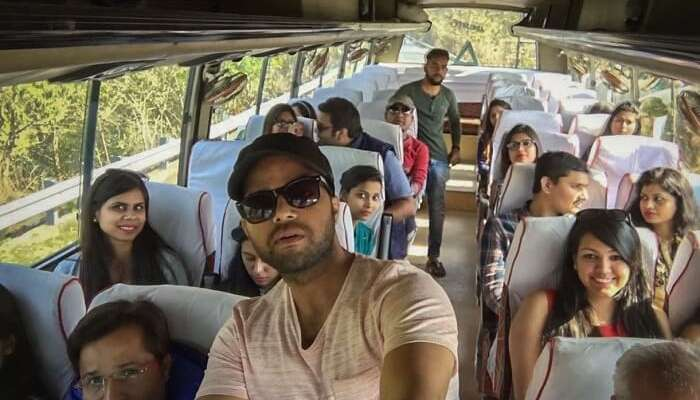 A group of travelers pose for a selfie in the bus taking them on their weekend trip from Delhi to Jim Corbett