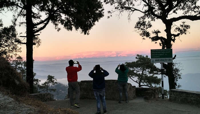 Travelers clicking pictures of the hills at sunset in Lansdowne