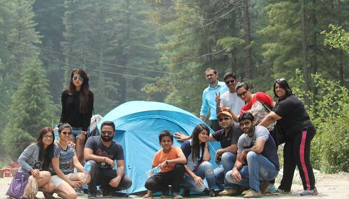 A group of travelers on one of the weekend trips from Delhi to Mcleodganj and Triund pose next a camp at the campsite