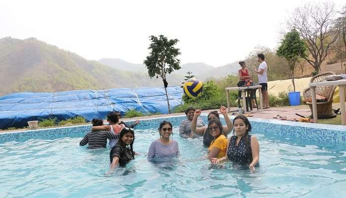 Travelers on their weekend trip to Rishikesh enjoying in a swimming pool in the camp resort