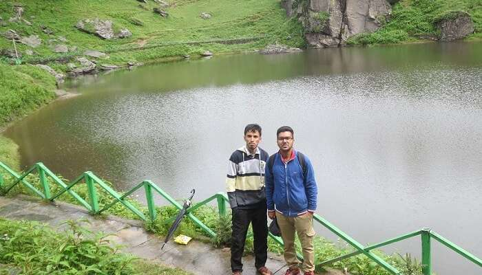 Two travelers standing next to a famous lake in Tirthan Valley