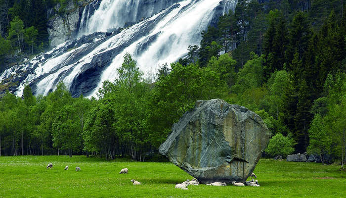 a giant stone on a green field with a waterfall