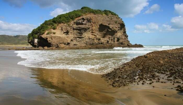 A picturesque cliff by the beach at the Bethells Beach near Auckland