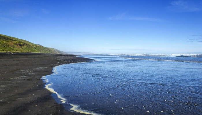 The black sand by the Kariotahi Beach in Auckland