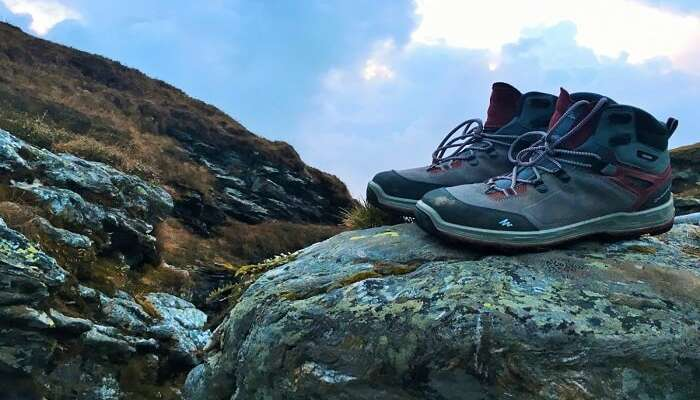 Trekking shoes kept on a boulder overlooking mountains