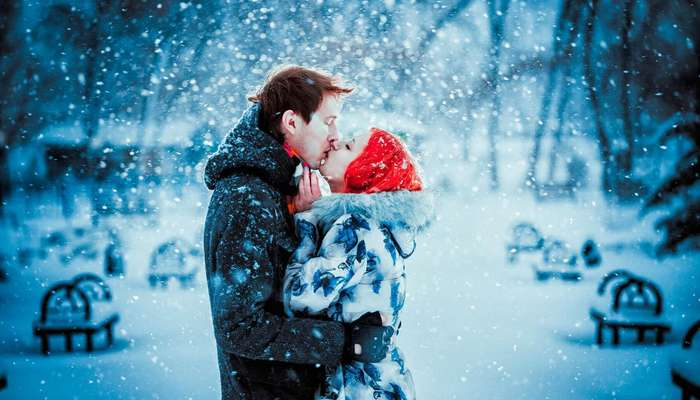 a couple kissing in snowfall - Valentine's Day Traditions
