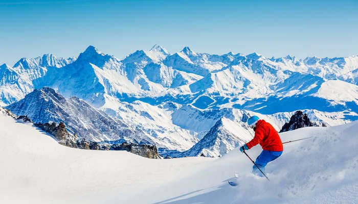 A man skiing in Dent Blanche slopes wearing red jacket